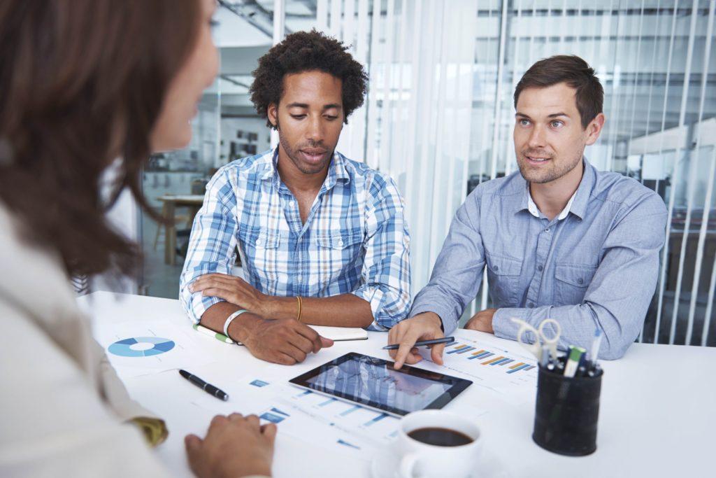 Zwei Männer unterhalten sich und zeigen dabei auf ein Tablet mit Statistiken und Grafiken.