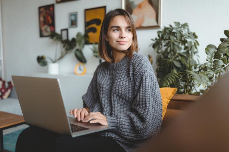Eine Frau sitzt vor ihrem Laptop in Home Office Umgebung und sieht aus dem Fenster.