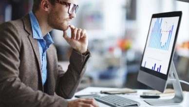 Male office worker looking at computer screen with data