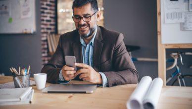 Ein Mann sitzt an seinem Schreibtisch und sieht in sein Smartphone.