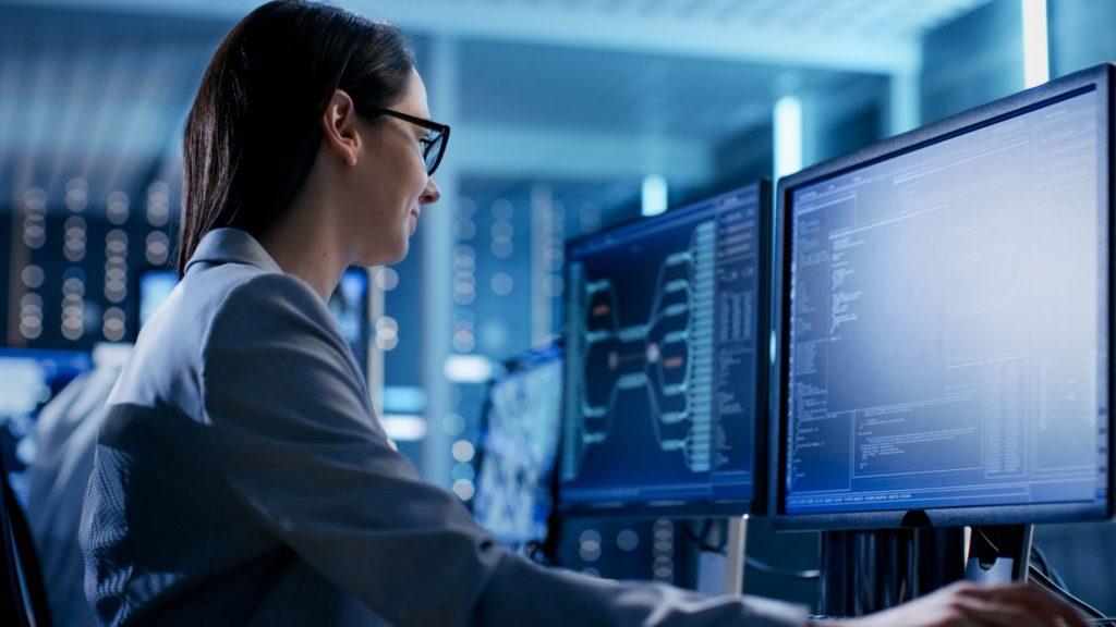 Eine Frau sitzt am Computer und kümmert sich um die Datensicherheit.