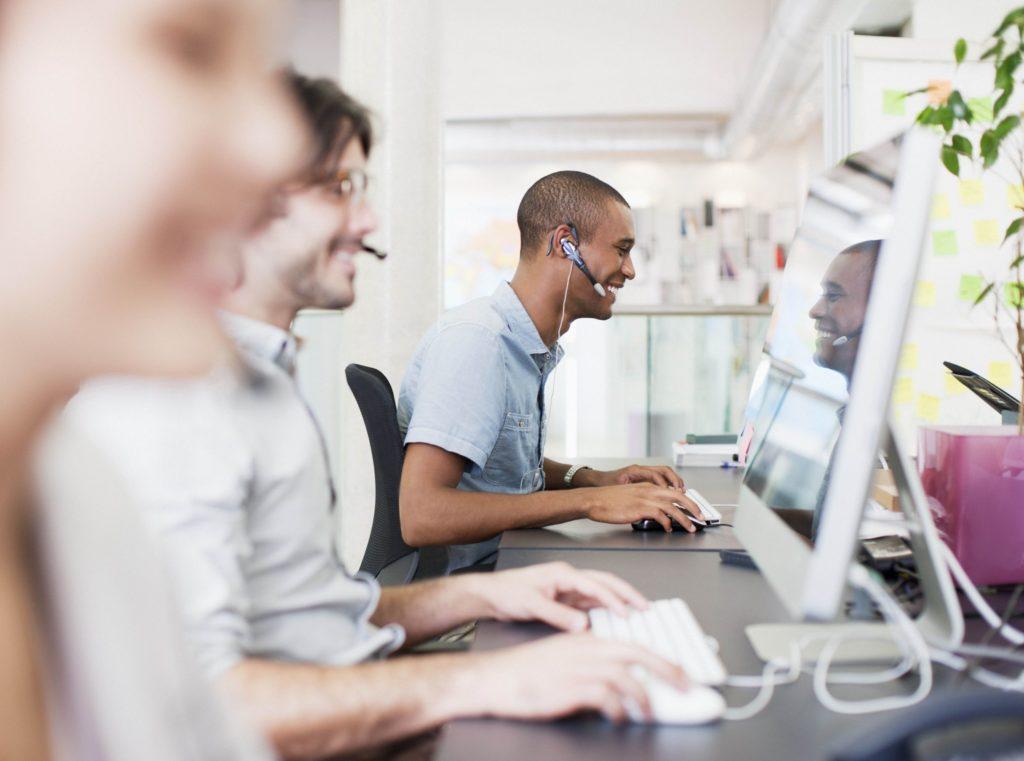 Menschen arbeiten in einem Büro und haben jeweils Headsets auf und blicken auf ihre Bildschirme.