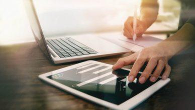 Es wird ein Notebook und ein Tablet gleichzeitig bedient. Auf beiden Geräten befinden sich Grafiken.